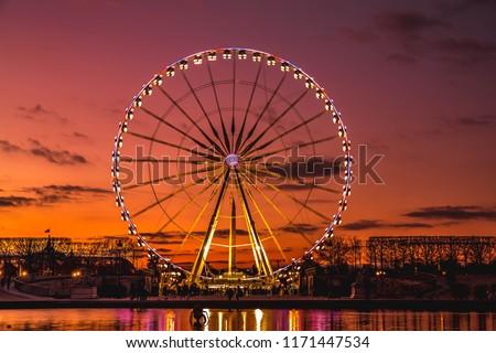 Illuminated Ferris wheel at sunset, Colorful sky and Ferris wheel. Royalty-Free Stock Photo #1171447534