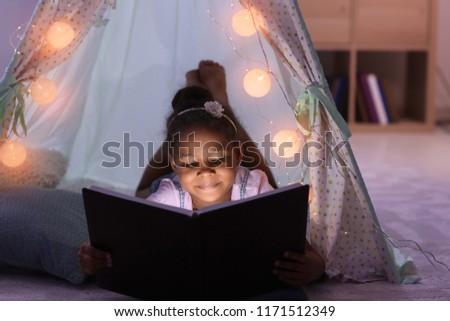 Little African-American girl reading bedtime story in hovel #1171512349