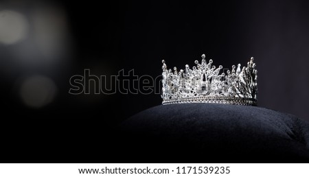 Diamond Silver Crown for Miss Pageant Beauty Contest, Crystal Tiara jewelry decorated gems stone and abstract dark background on black velvet fabric cloth, Macro photography copy space for text logo #1171539235