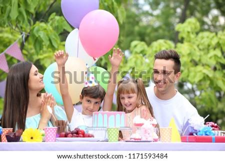 Happy family celebrating birthday at table outdoors #1171593484