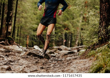 dirty runner athlete running down trail stones in woods #1171657435