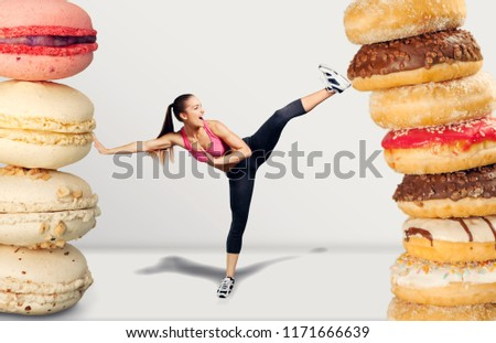 Fit young woman fighting off fast food #1171666639