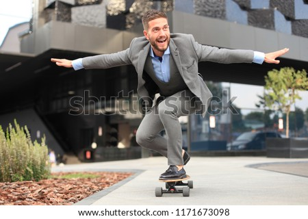 Confident young businessman in business suit on longboard hurrying to his office, on the street in the city #1171673098
