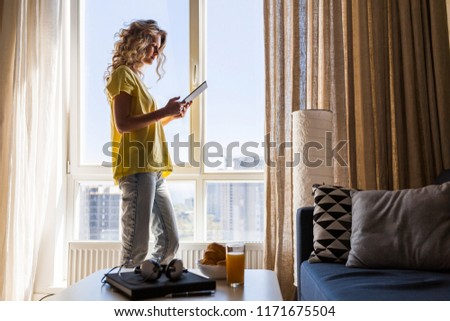 young pretty blond woman at home working online on tablet, using internet, smiling, freelance, girl standing at window, morning, reading #1171675504