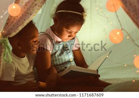 Little African-American children reading bedtime story in hovel #1171687609