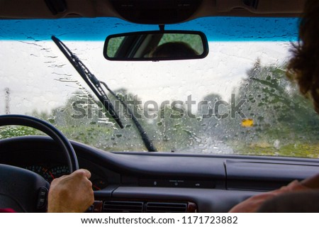 A couple sitting in the car while it is raining heavily. The windshield wipers have a lot to do and are busy to clear the window view to drive safely Royalty-Free Stock Photo #1171723882