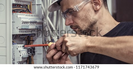 a male electrician works in a switchboard with an electrical connecting cable, connects the equipment with tools, the concept of complex work, space for text #1171743679