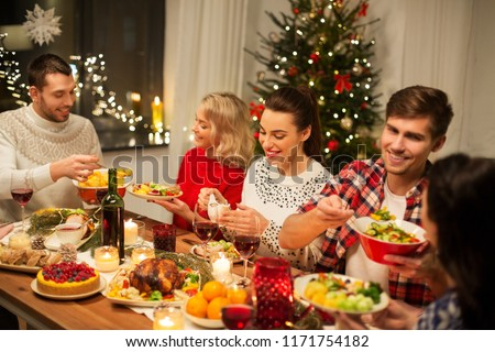 holidays and celebration concept - happy friends having christmas dinner at home and eating food #1171754182