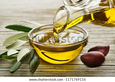 Bottle of Olive oil pouring in a glass bowl with olives and branch #1171769116