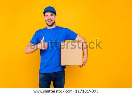 Portrait of handsome attractive cheerful bearded deliver with stubble in blue uniform holding card-board box, showing thumbs-up, isolated over bright vivid yellow background