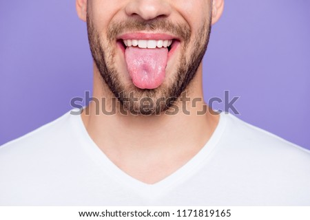 Close-up cropped portrait of attractive, trendy, stylish, toothy man with healthy teeth, showing tongue out, over pastel violet purple background Royalty-Free Stock Photo #1171819165