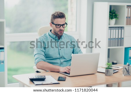 Portrait of smart handsome man in spectacles sits in a stylish casual blue shirt on comfortable chair at the wooden desk on workplace #1171820044