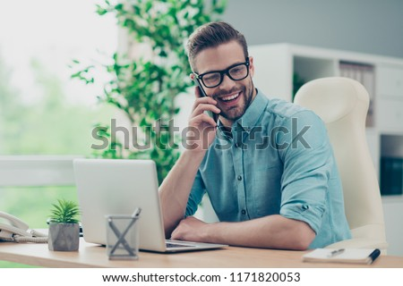 Bearded, nice, smart, clever, good-looking man in trendy black spectacles sits in casual stylish blue shirt at the wooden desk talking on the phone and looking away on pause, rest, relax #1171820053