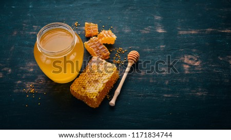 Honey in a jar and a honeycomb. On a black wooden background. Free space for text. Top view. #1171834744