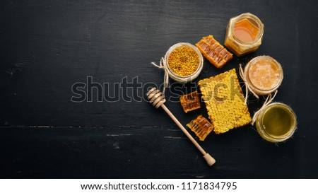 A set of honey and bee products. Honey in honeycomb. On a black wooden background. Free space for text. Top view. #1171834795