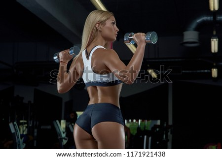 A young smart girl posing in the gym. Dark background. #1171921438