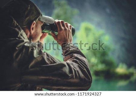 Caucasian Hunter in Masking Camouflage Uniform with Binoculars. Hunter Spotting Game. Poacher or Soldier Clothing. #1171924327