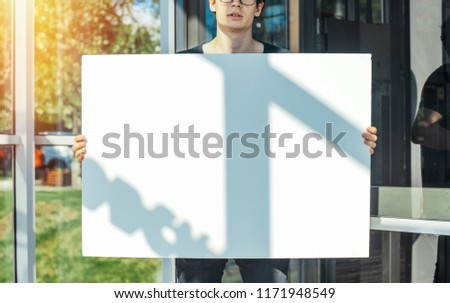 Close up of Young Attractive Man Holding Blank Сanvas Poster Or Placard At Metro Station. Concept Of Active Сitizenship
