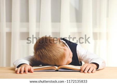 Tired schoolboy sleeps with book on desk. Concept school. #1172135833