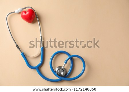 Medical stethoscope and red heart on light background. Cardiology concept #1172148868