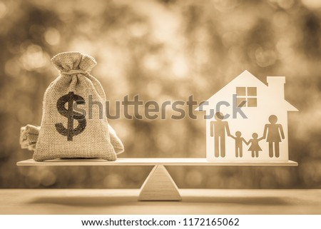 Legacy / inheritance or death tax concept : US dollar bag, a house and family members e.g father, mother, son, daughter on a balance scale, depicts a tax paid by person who inherits money or property. #1172165062