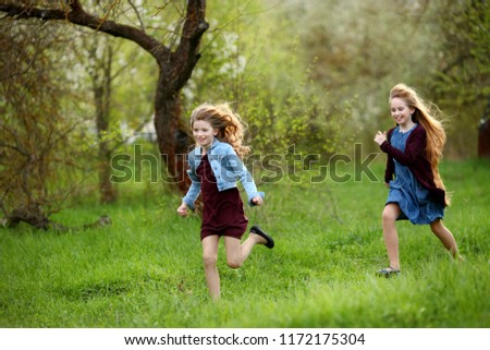 Two little girls running on the road in the park on a sunny summer day. Cute babies #1172175304