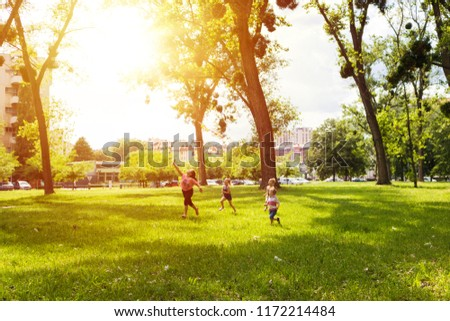 Group of kids running while flying kite in nature and having fun together. #1172214484