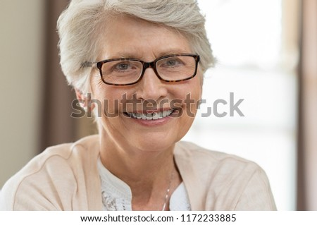 Portrait of a happy senior woman wearing eyeglasses. Beautiful elderly woman with eyeglasses smiling at home. Mature woman with gray hair wearing specs while looking at camera. #1172233885
