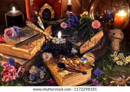 Still life with old witch books, antique lamp, black candles, voodoo doll and ritual objects. Mystic background with ritual esoteric objects, occult, fortune telling and halloween concept #1172298181