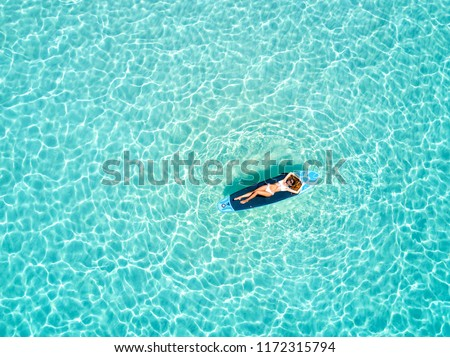 Blonde vacations woman in bikini takes a sunbath on a surfboard over the tropical, turquoise waters of the Maldives #1172315794