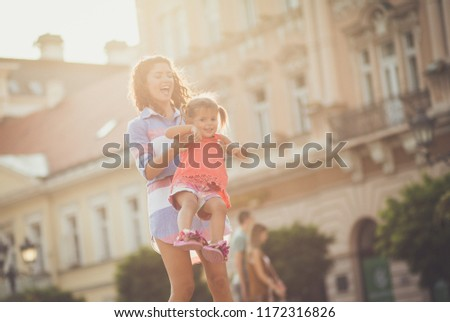 We are happy when we are together. Young mother having fun with her little daughter on city street. Copy space. Close up.  #1172316826