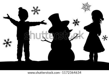 A Christmas winter silhouette scene with a kids having fun in the snow building a snowman with snowflakes falling