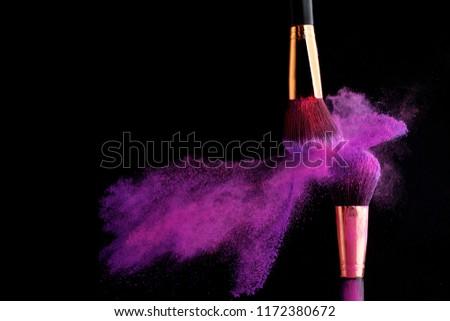 Make-up brush with colorful powder splashes explosion on black background #1172380672