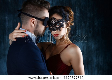 Sexy woman female in black carnaval mask red expensive dress and gold earnings seduces millionaire man male in suit, bow tie and black carnaval mask. Sex, tempts, harassment, sexism, seduction issues #1172399812