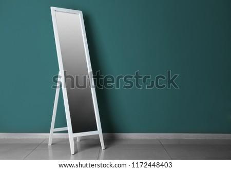 Big stylish mirror near color wall in empty room #1172448403