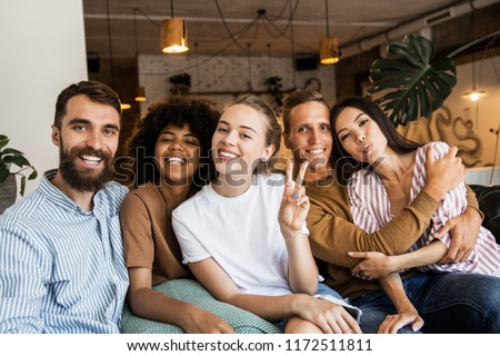 Happy multi ethnic young people looking at camera, smiling diverse friends or students showing peace sign, multicultural millennials posing together at meeting, tolerance and racial equality concept #1172511811
