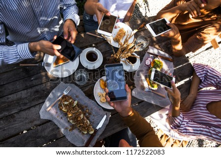 Top view of young beautiful people taking photos of their food while sitting at the table and having picnic outdoors #1172522083