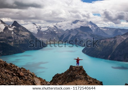 Woman standing on top of the Mountain overlooking a beautiful glacier lake. Taken on Panorama Ridge, Garibaldi, Near Whister, BC, Canada. Royalty-Free Stock Photo #1172540644