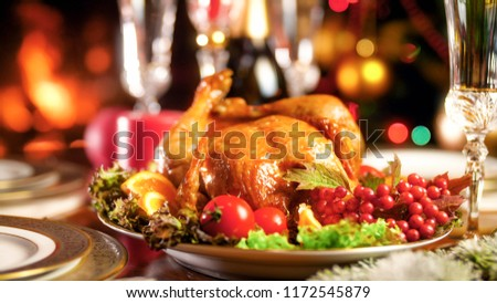 Closeup image of hot tasty chciken with vegetables and cranberries on dinner table #1172545879