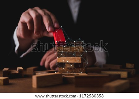 business man try to build wood block on wooden table and black background business organization startup concept #1172580358