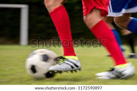 Close-up on two men playing soccer outdoors and running after the ball. #1172590897