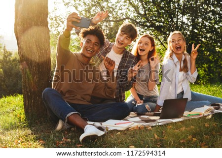 Group of happy multhiethnic students doing homework together at the park, using laptop computer, taking a selfie with mobile phone #1172594314