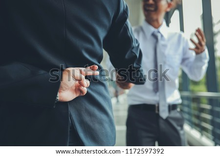 Trickery Concept.Business partners shaking hands with one of them holding fingers crossed behind back. #1172597392