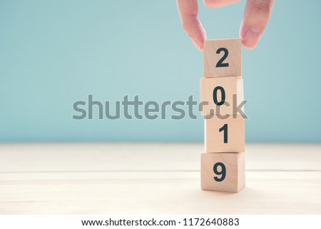 Hand of man putting wood cube shape with text new year 2019, copy space. #1172640883