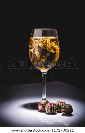 glass of traditional chinese flowering tea with tea balls on table isolated on black #1172700211
