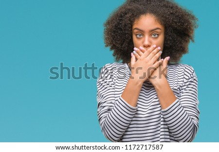 Young afro american woman over isolated background shocked covering mouth with hands for mistake. Secret concept. #1172717587