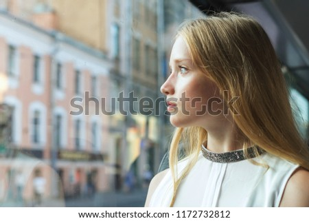 beautiful girl sitting in the bus and looking through the window #1172732812