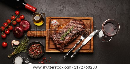 Grilled Striploin beef steak on wooden board with glass of wine, vegetables, herbs and spices on dark stone background. Top view #1172768230