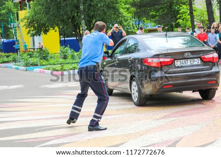 A policeman, a road policeman in blue uniform, threatens with a pistol, aims at the driver's criminal. Belarus, Minsk, 08.08.2018. #1172772676