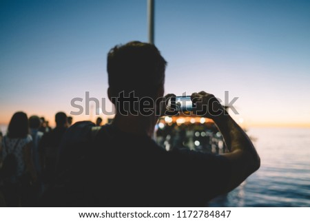 Back view of man taking picture of evening scenery near sea using modern mobile phone camera, male tourist making photo in night twilight photographing in dark with smartphone  in both hands
